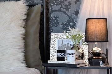 Realizace dámská ložnice černá postel s polštáři a kovový noční stolek s lampou
