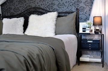 Realizace dámská ložnice kovová postel a stolek s lampou a květinami